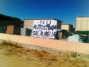 Uno striscione contro l'autostrada che si sovrapporrebbe alla statale Aurelia